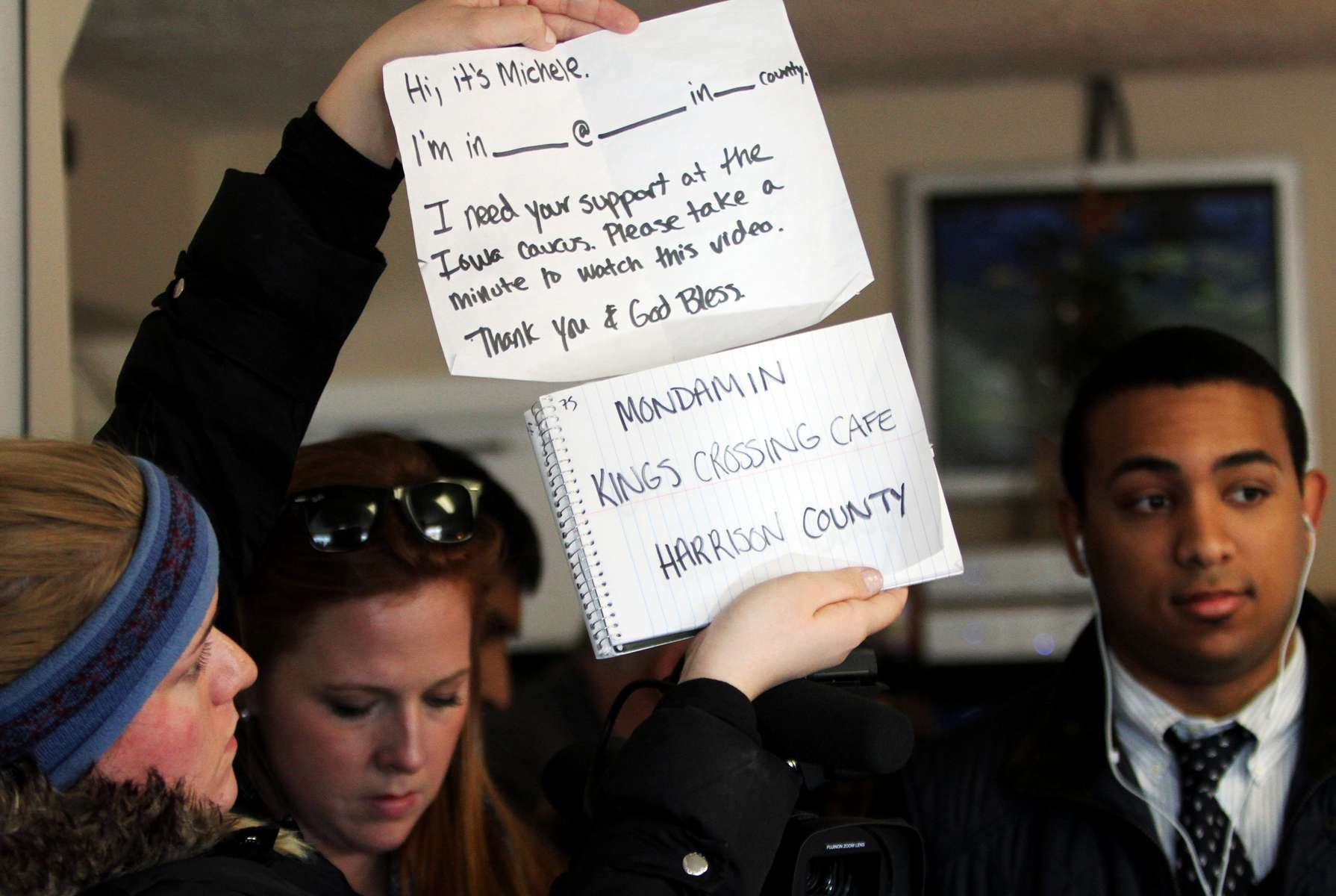 Michele Bachmann staff member Whitney Clark holds cue cards for Bachmann at King\'s Crossing Cafe in Mondamin, Iowa. Bachmann\'s campaign is producing short videos from all of the stops during her bus tour.