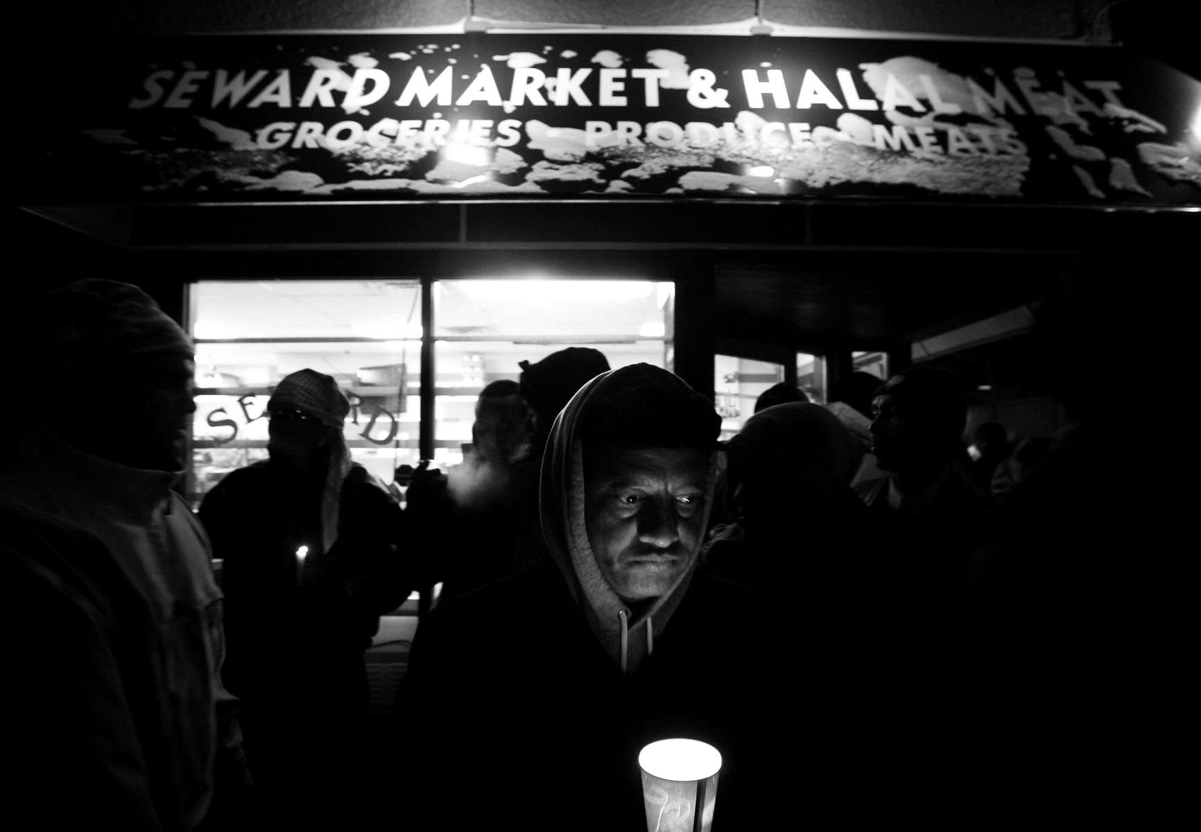 Endale Kebede of Columbia Heights lit a candle during a vigil in Minneapolis. Hundreds of people gathered at Seward Market and Halal Meats on E. Franklin Avenue in Minneapolis  to remember the three young men killed at the market.