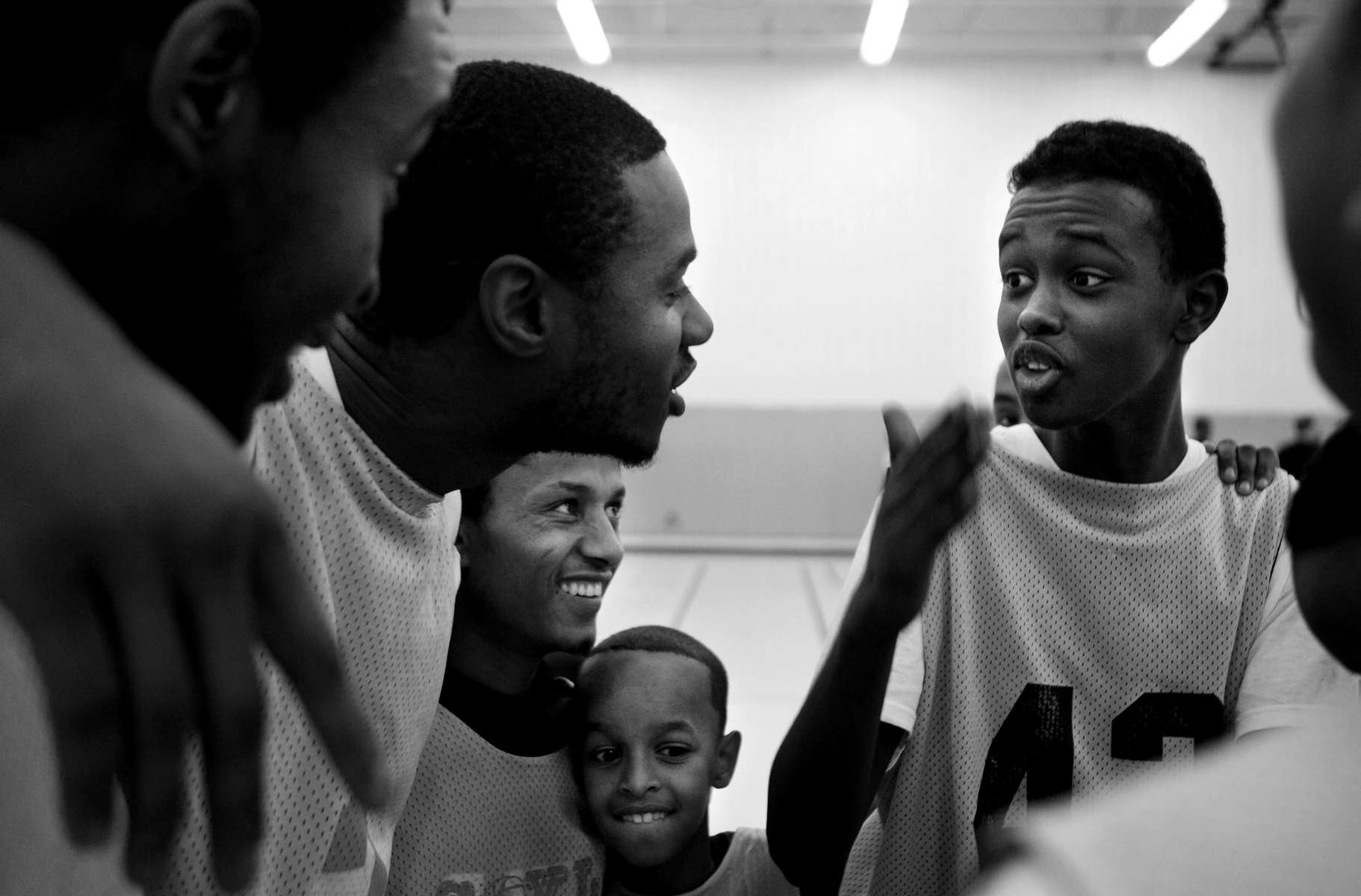 Mohamed Jama, 16, right, jokes with his teammates before a basketball game at The Brian Coyle Community Center in Minneapolis. Jama has taken an active role in leading the young people of his community.