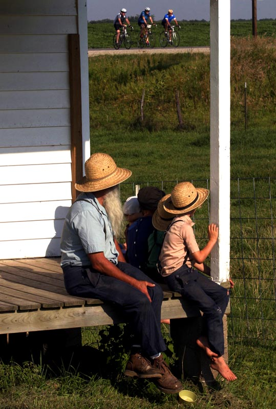 An Amish elder and his children watch as RAGBRAI riders pedal past their rural home in Lebanon, Iowa.
