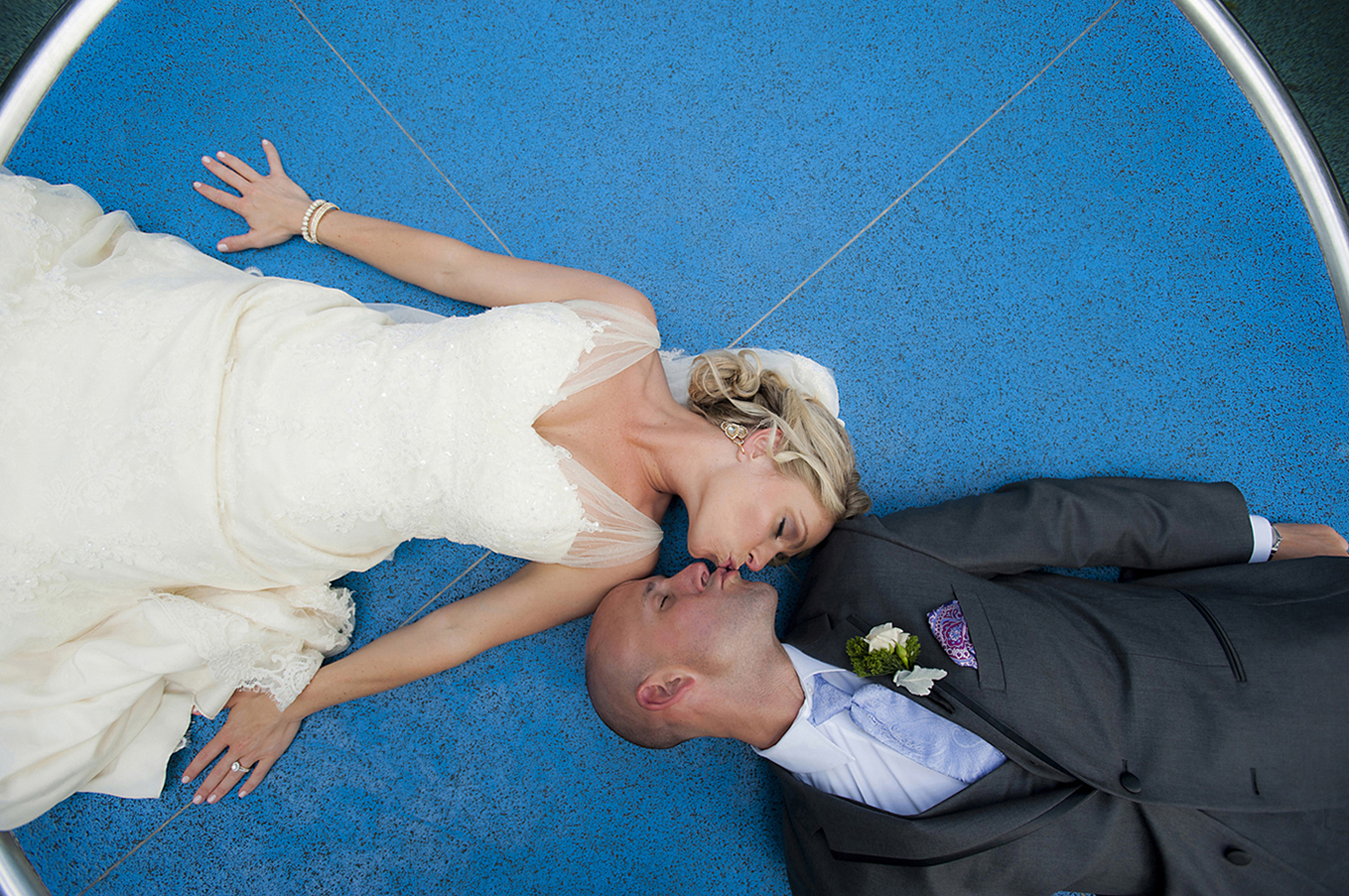 creative portrait of bride and groom at Pier C in Hoboken with blue background. Hoboken wedding photographers. NJ wedding photographers
