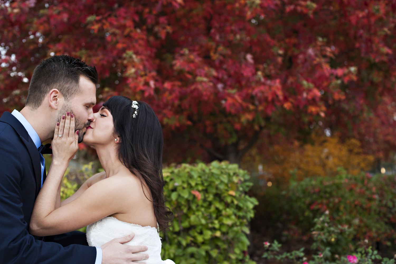 Bride and groom kissing on their wedding day against fall leaves. Hoboken wedding photos