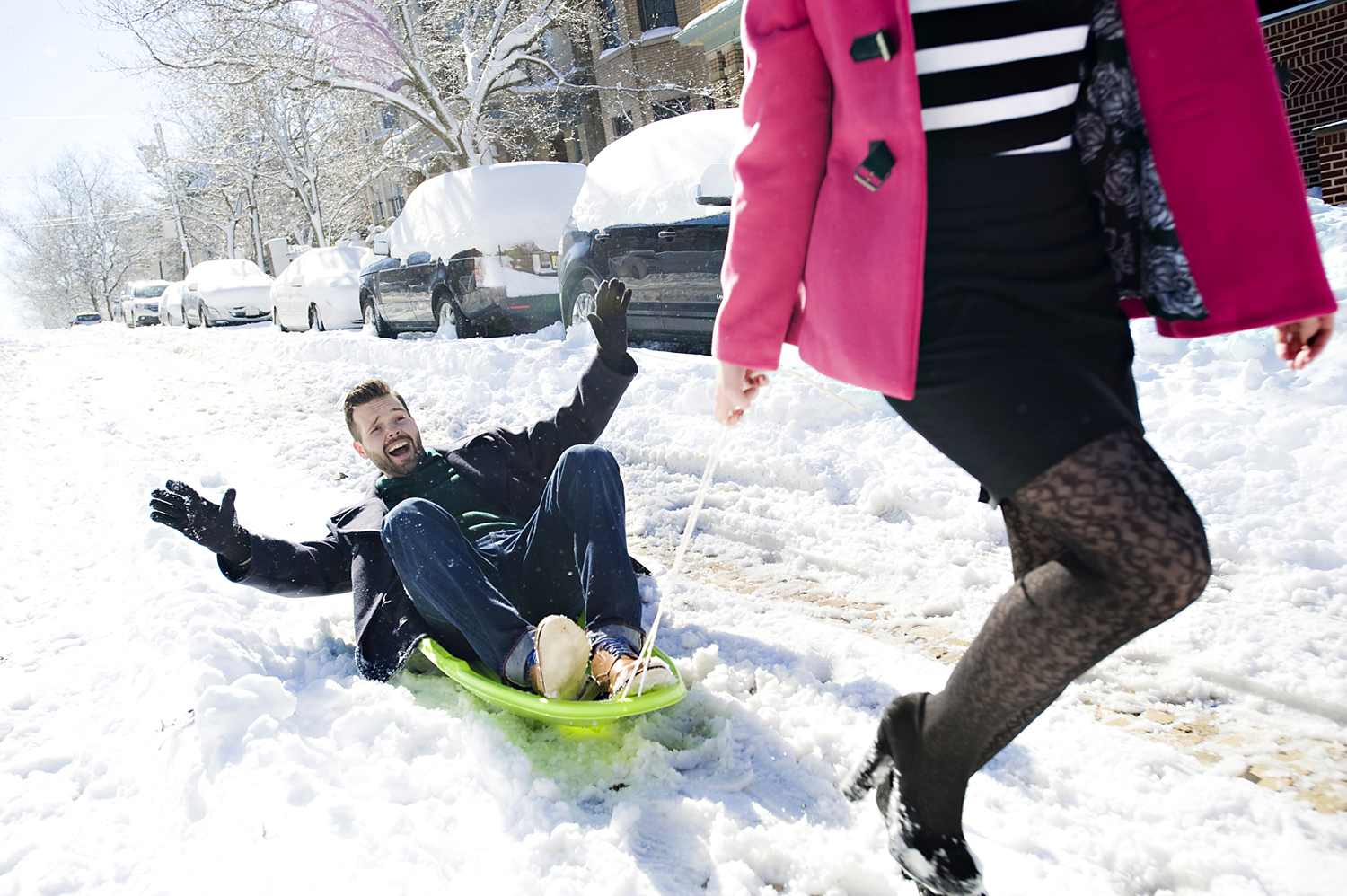 engaged couple sledding during their snowy Hoboken engagement session. Hoboken wedding photographers