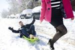 engaged couple sledding during their snowy Hoboken engagement session. Hoboken wedding photographers