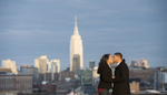 Couple kissing during engagement session in Hoboken with NYC skyline behind them. Hoboken wedding photographers