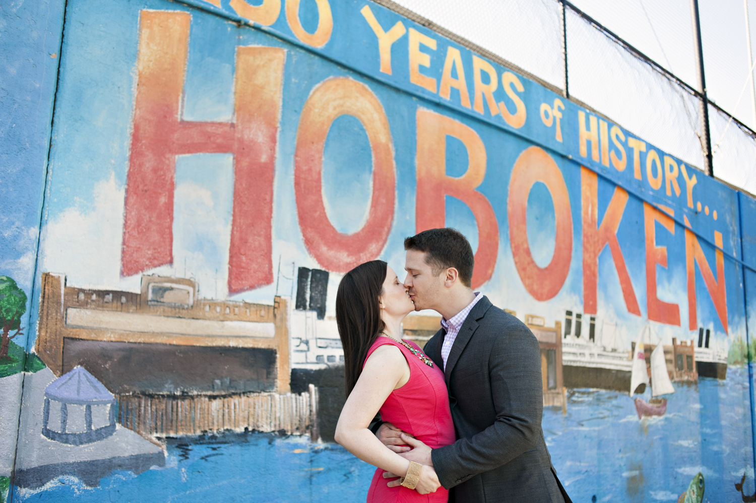 engaged couple in front of Hoboken mural during their engagement session. Hoboken wedding photographers
