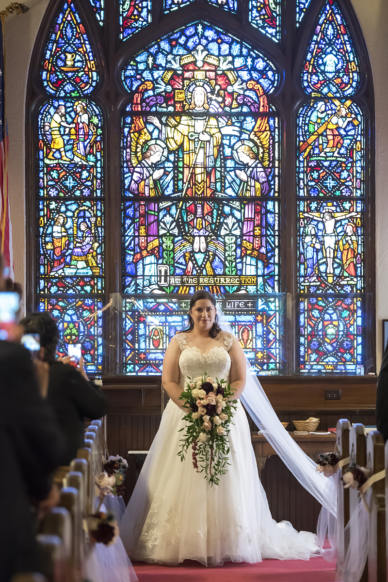 Bride walks down the aisle against the backdrop of a gorgeous stained glass window at the start of church wedding ceremony in Hawthorne, NJ.