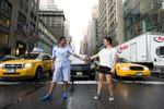 Couple standing in NYC street against yellow cabs for engagement photos. Gay-friendly NYC wedding photographers