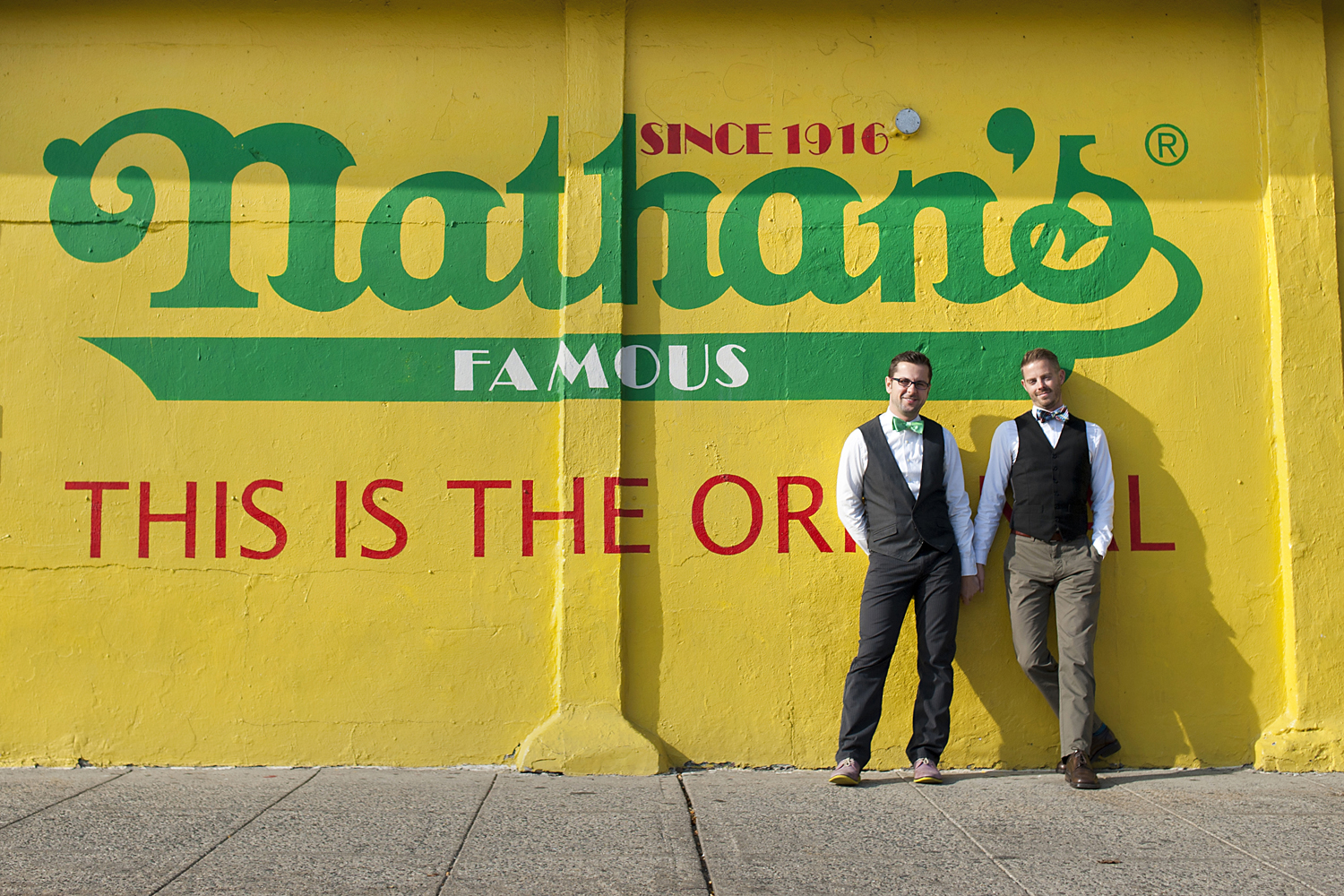 grooms in front of Nathan's Hot Dog in Coney Island. NYC wedding photographers