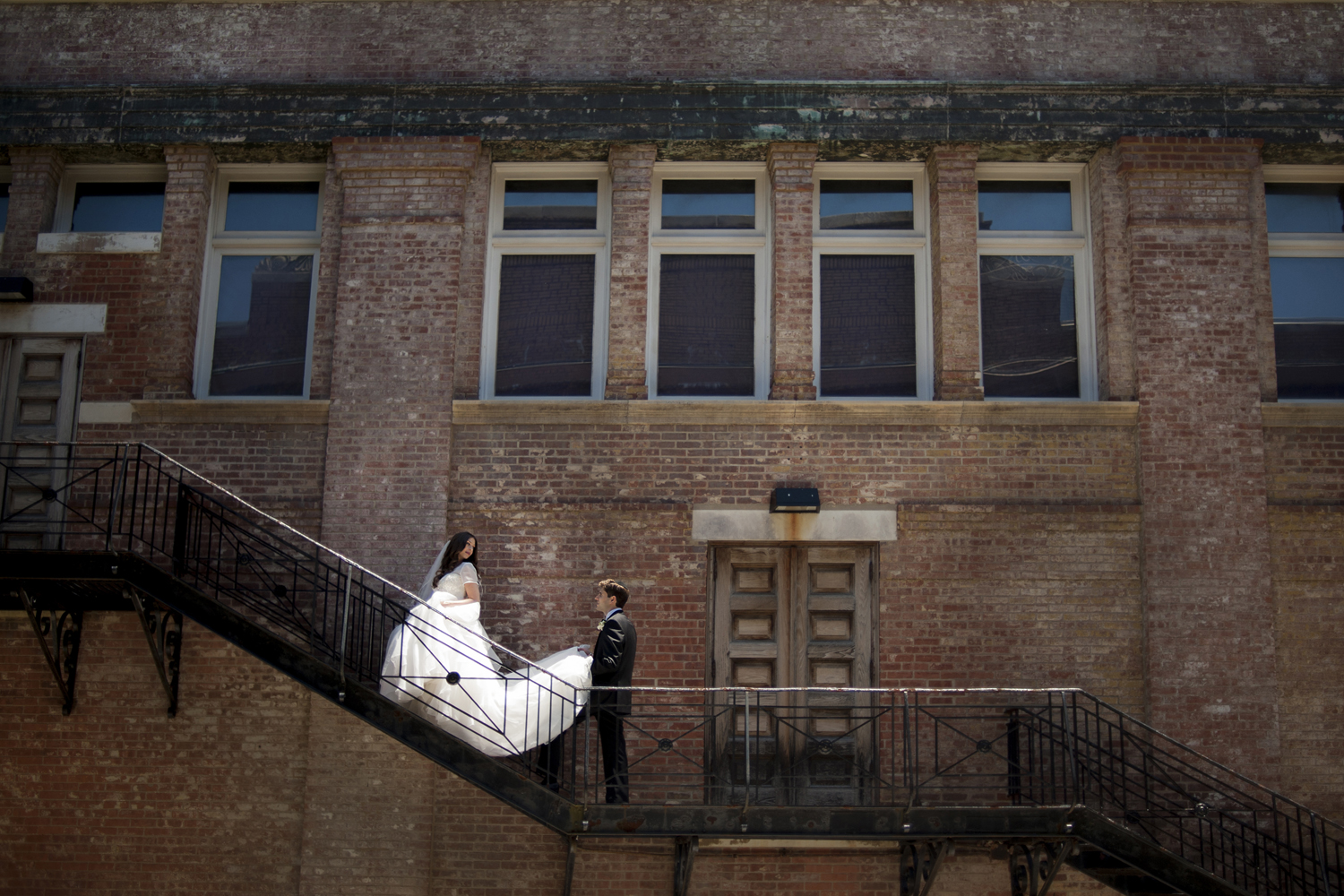 Portrait of bride and groom on their wedding day on fire escape at Celebrate Snug Harbor in Staten Island