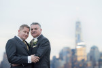portrait of grooms on wedding day with NYC skyline behind them. NYC gay wedding photographer
