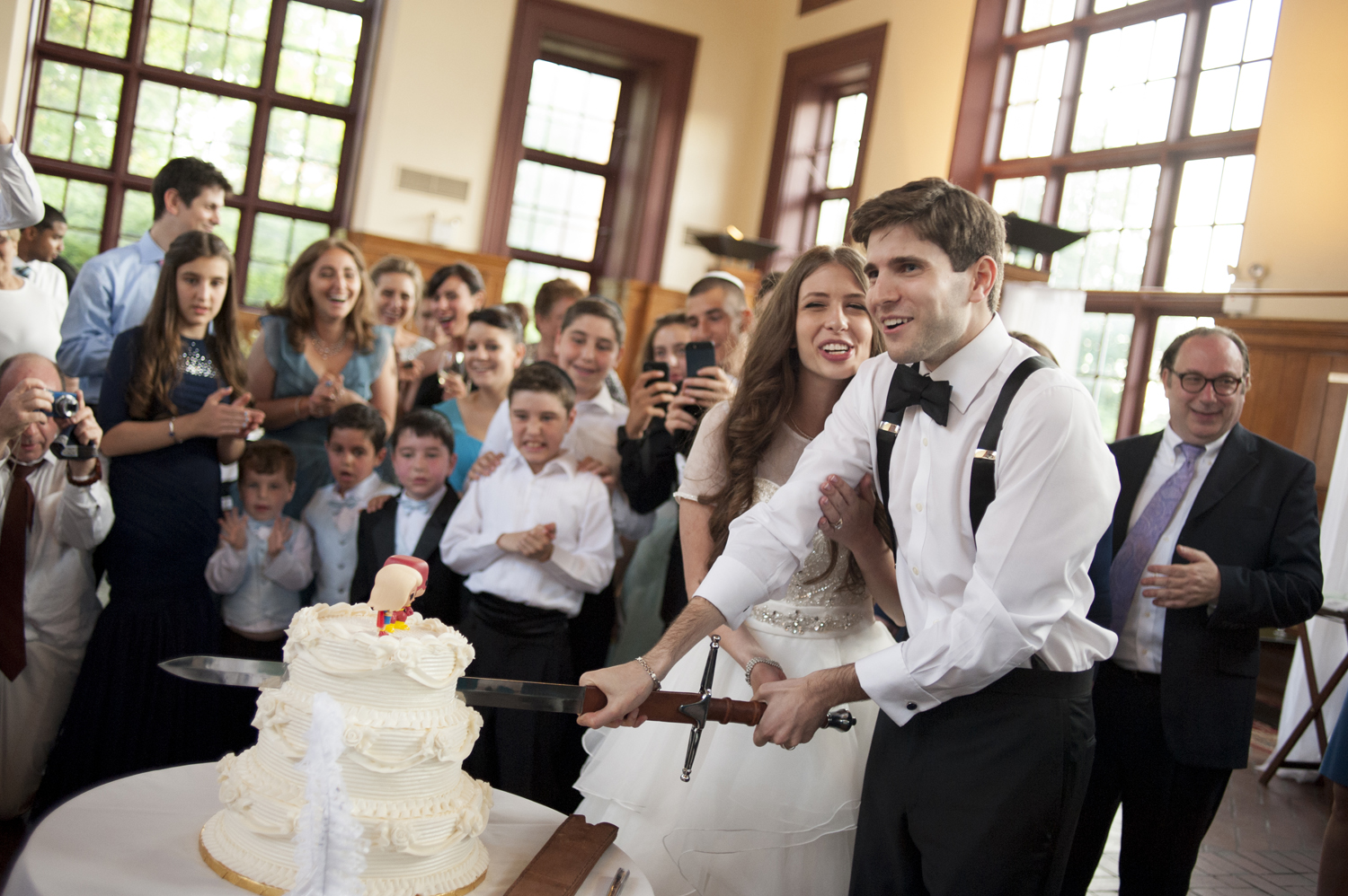groom cuts wedding cake with sword at Celebrate at Snug Harbor