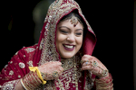 Hindu bride laughing as she adjusts her red and gold outfit