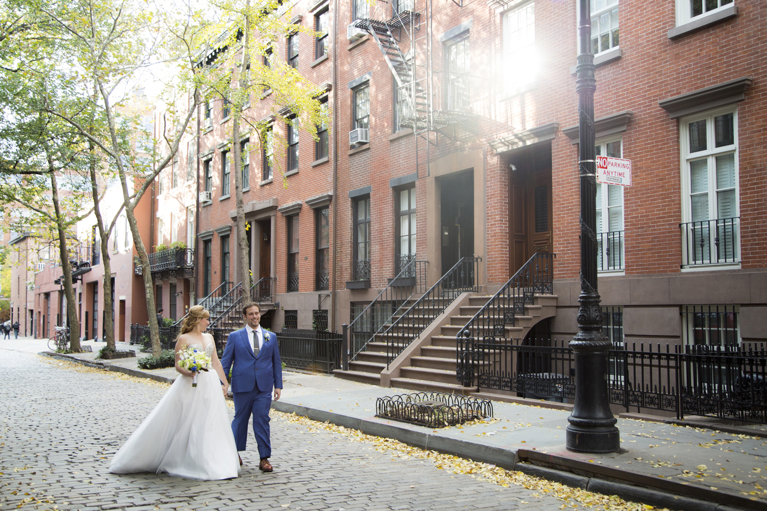 bride and groom walking on cobbestone street in west village, NYC on their wedding day. NYC wedding photographers