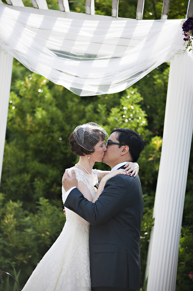 bride and groom kissing at conclusion of wedding ceremony at Queens Botanical Garden. NYC wedding photographers