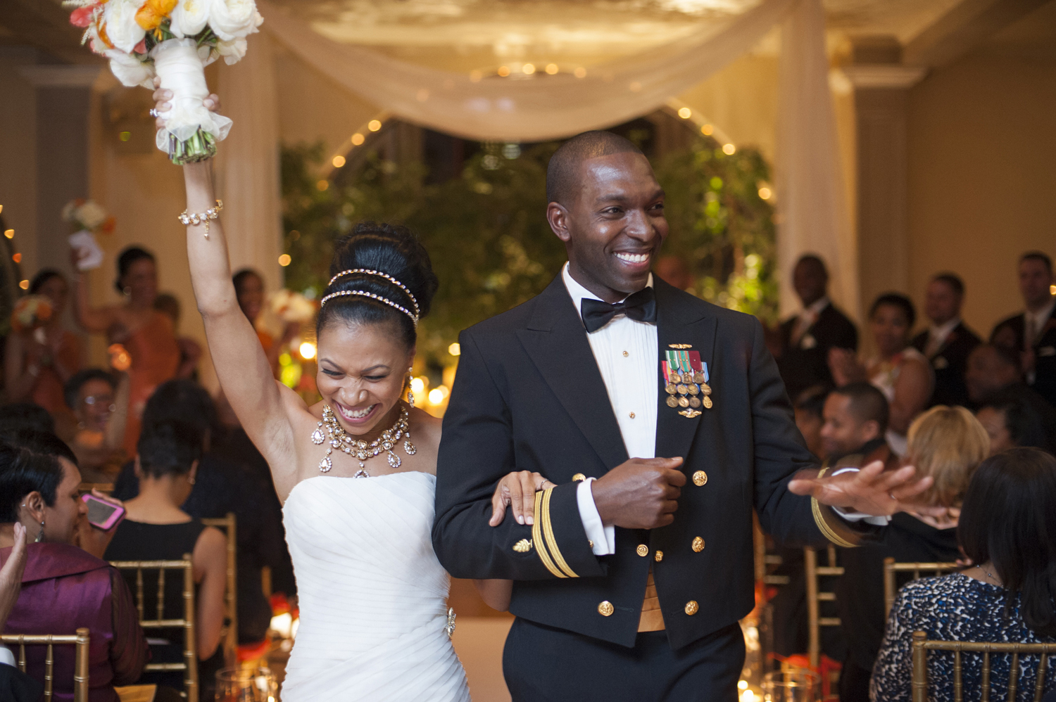 black bride and groom celebrate after their are wed at their ceremony at Manhattan Penthouse. Groom is in Navy uniform.