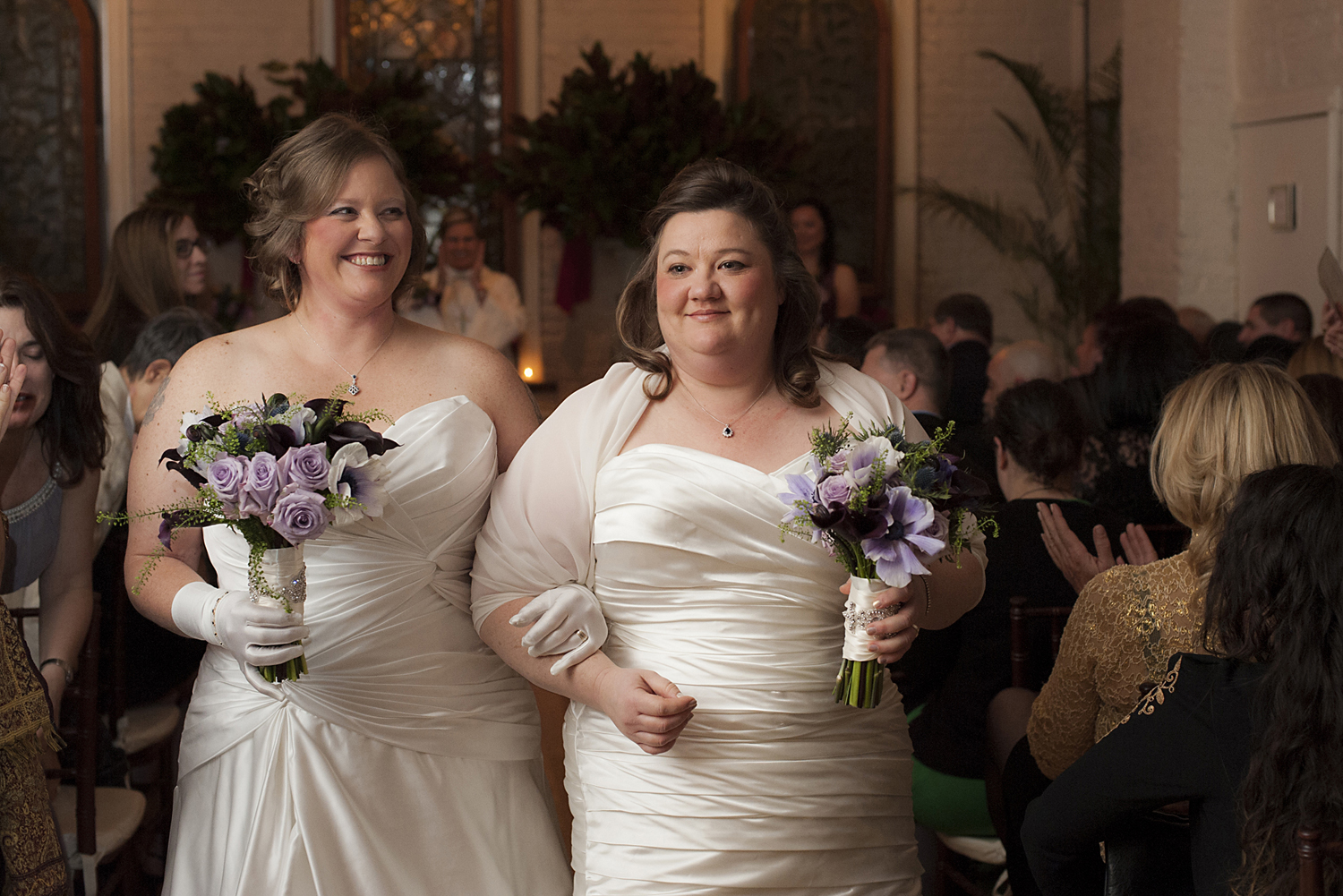 Brides walk down aisle after their wedding ceremony at Alger House. Gay NYC wedding photographer