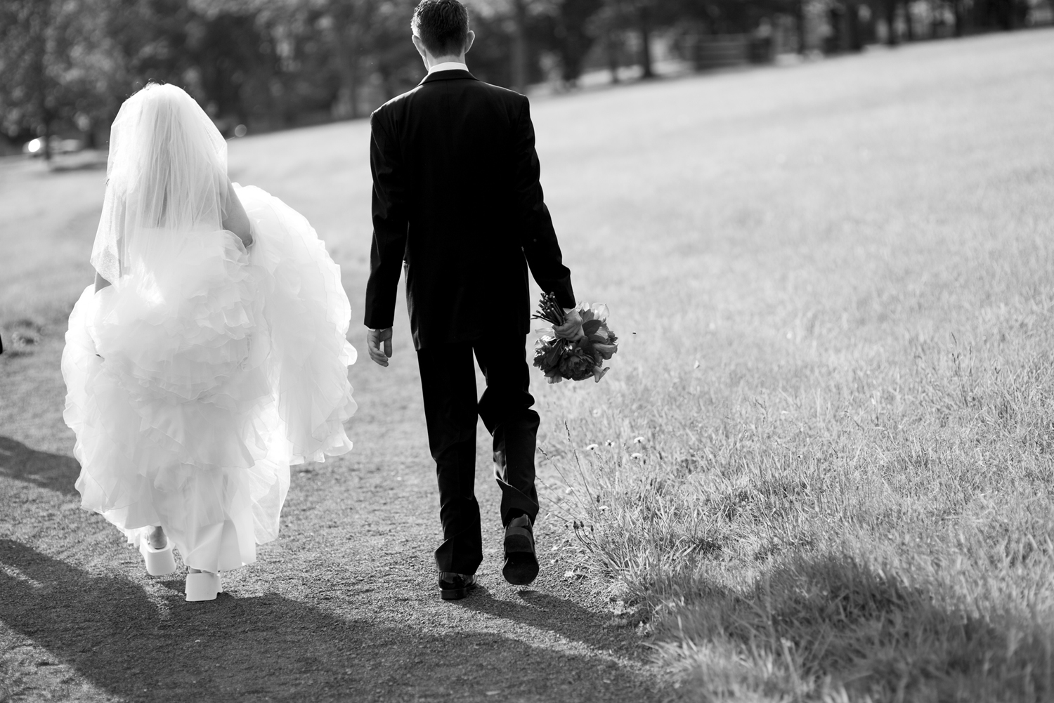 black and white image of bride and groom walking in park on their wedding day. NJ wedding photographers