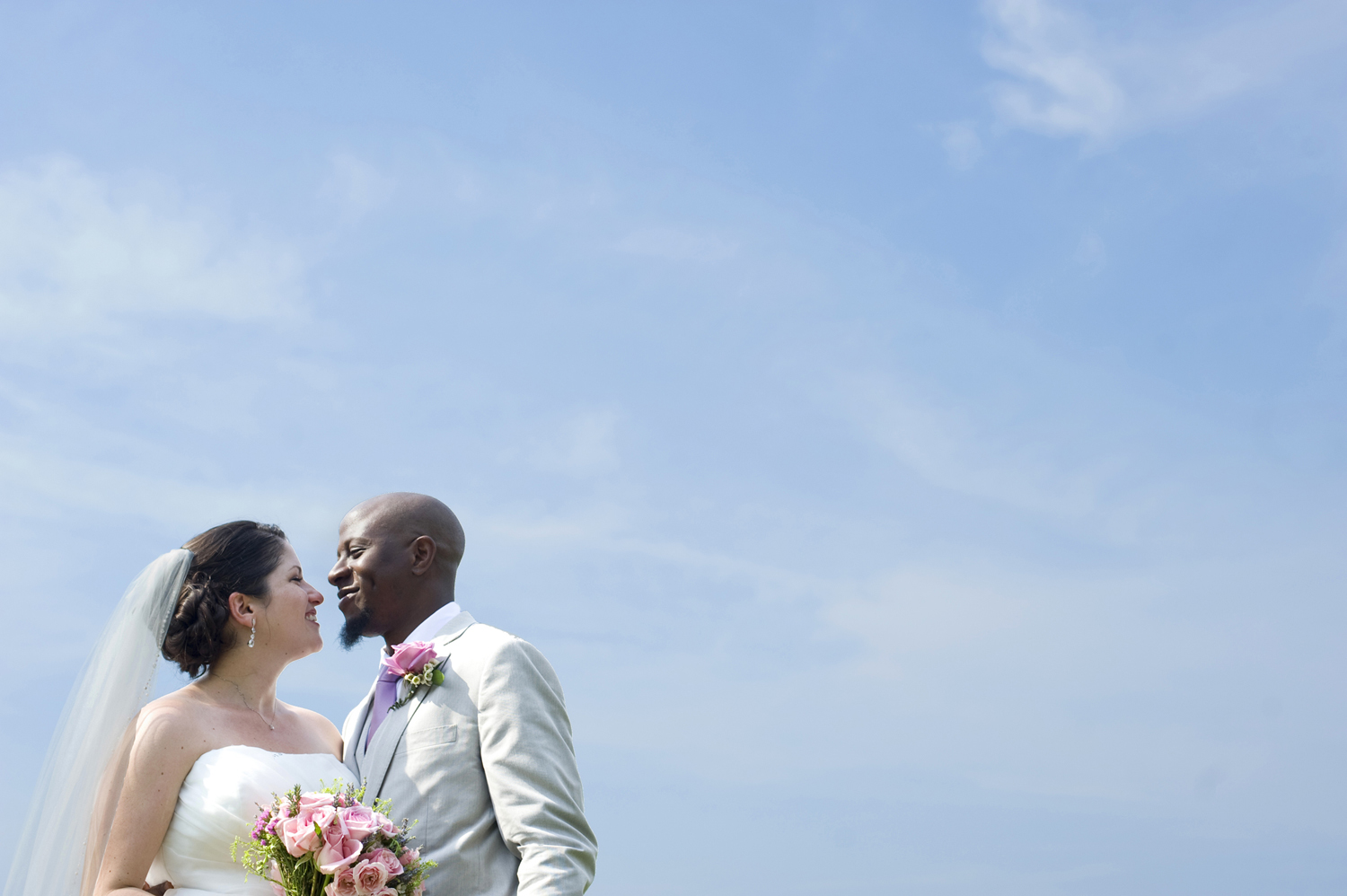 portrait of bride and groom against blue sky at The Water Witch Club at Monmouth Hills on their wedding day. Jersey Shore wedding photos