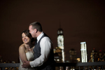 Portrait of bride and groom laughing against the NYC sklyine at night on their wedding day. Hoboken wedding photographers