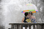 Brides kissing in the snow under colorful umbrella during their winter wedding at Lambertville House. Lesbian wedding