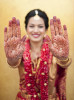 indian bride showing off her henna on her hands.