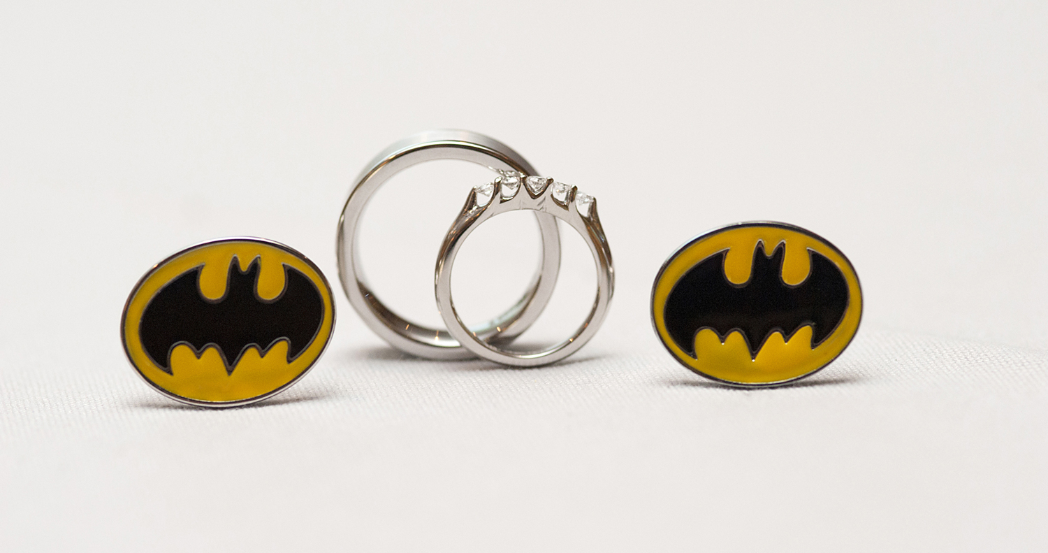 Creative ring shot of wedding rings with Batman cufflinks at Preakness Hill Country Club. Hoboken Wedding Photographers