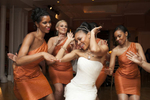 bride and orange-dressed bridesmaids dance-off at reception at wedding at Manhattan Penthouse. NYC wedding photographers