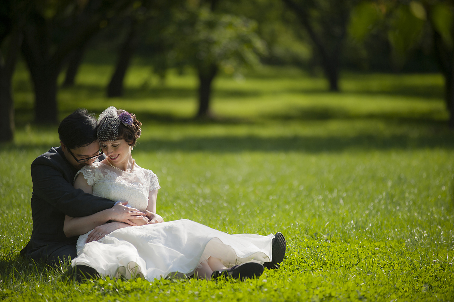 Bride and groom sitting in grass at Queens Botanical Garden after their beautiful summer wedding. NYC wedding photos