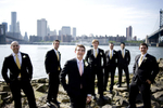 Groomsmen in Brooklyn with NYC skyline behind them on wedding day. NYC wedding photography