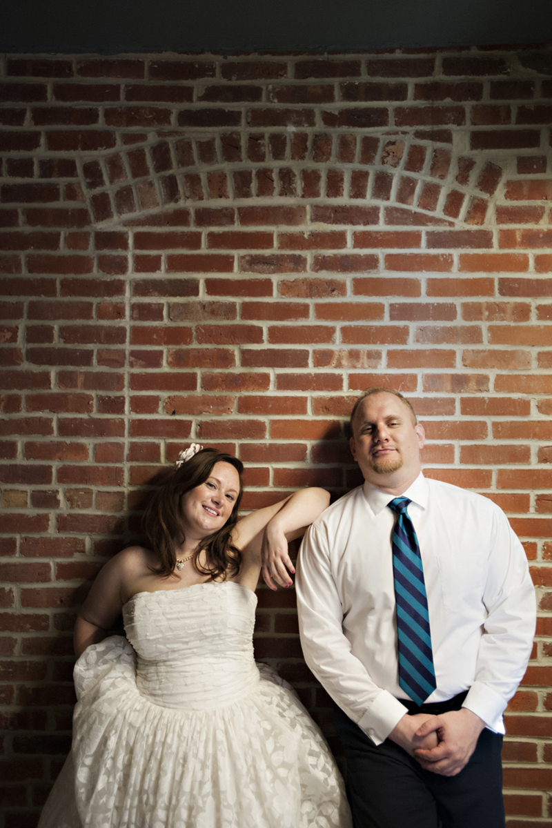 Portrait of bride and groom against brick wall at BLDG 92, Brooklyn Navy Yard. NYC wedding photographers