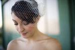 bride with birdcage veil in front of train station in Liberty State Park before her wedding at Liberty House. NJ wedding photographers
