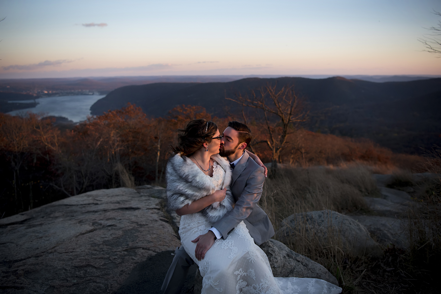 bride and groom kissing against the sunset sky at Bear Mountiain on their wedding day