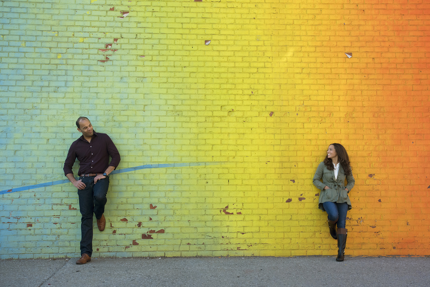 engaged couple against rainbox mural in DUMBO Brooklyn during their engagement session. Brooklyn wedding photographers