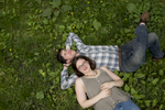 Engaged couple laying on the grass during their engagment session in Central Park