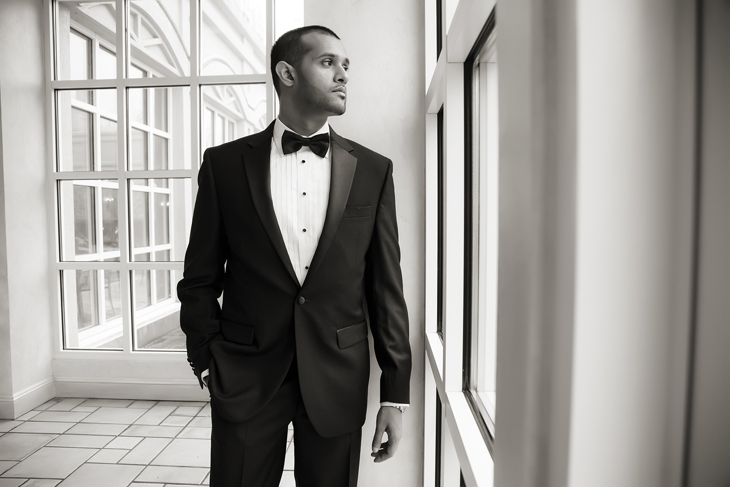 dapper groom staring out the window on wedding day at Hilton Pearl River