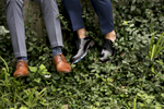 grooms feet dangling next to each other in park in Hoboken