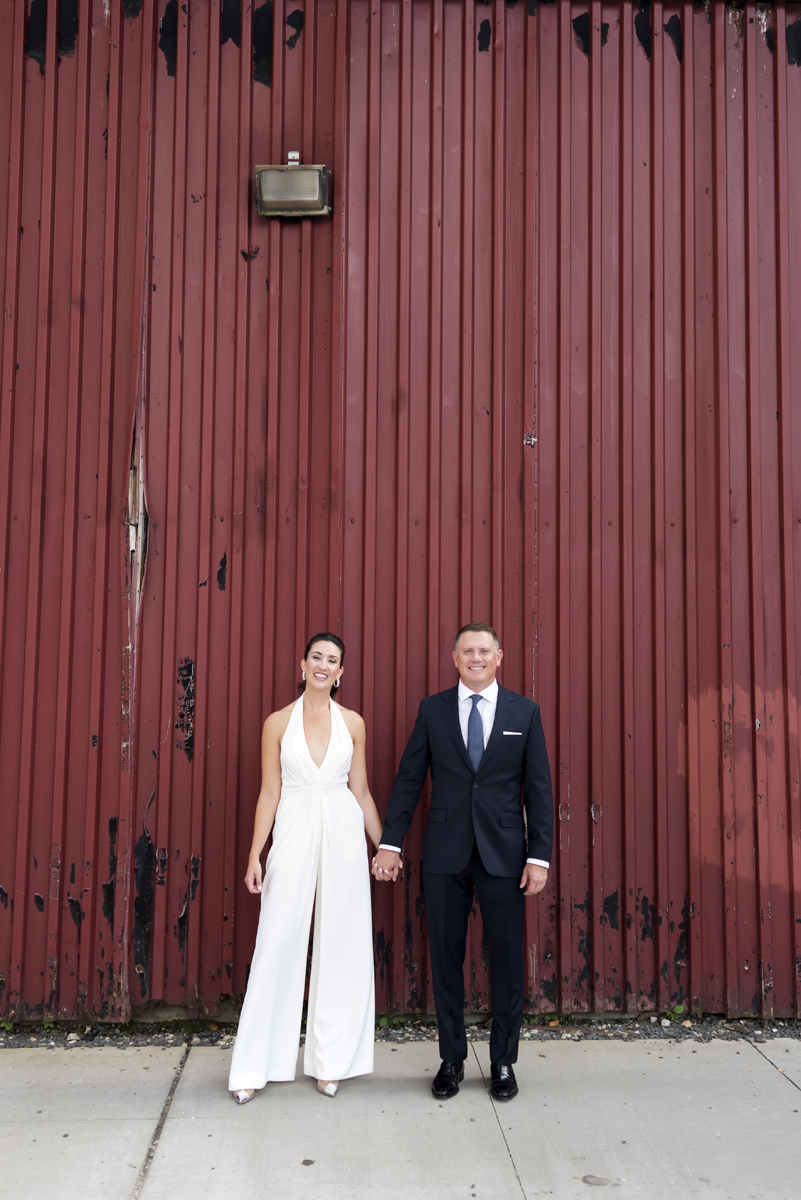 bride and groom against red wall in Hoboken before their wedding celebration at Kolo Klub
