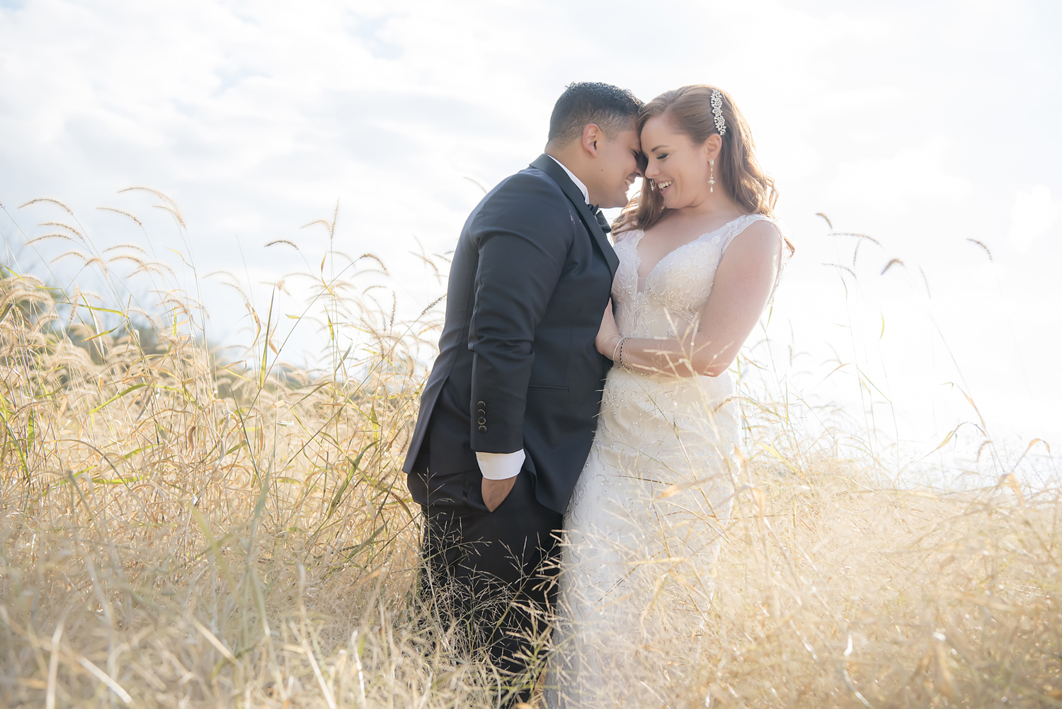 bride and groom kissing in cornfield at Hotel du Village