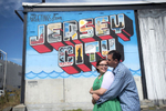 engaged couple in front of Jersey City mural during their engagement session. Jersey City wedding photographers