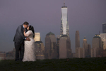 creative portrait of bride and groom in front of NYC skyline at night at Liberty State Park. Jersey City wedding photographers. NJ wedding photographers