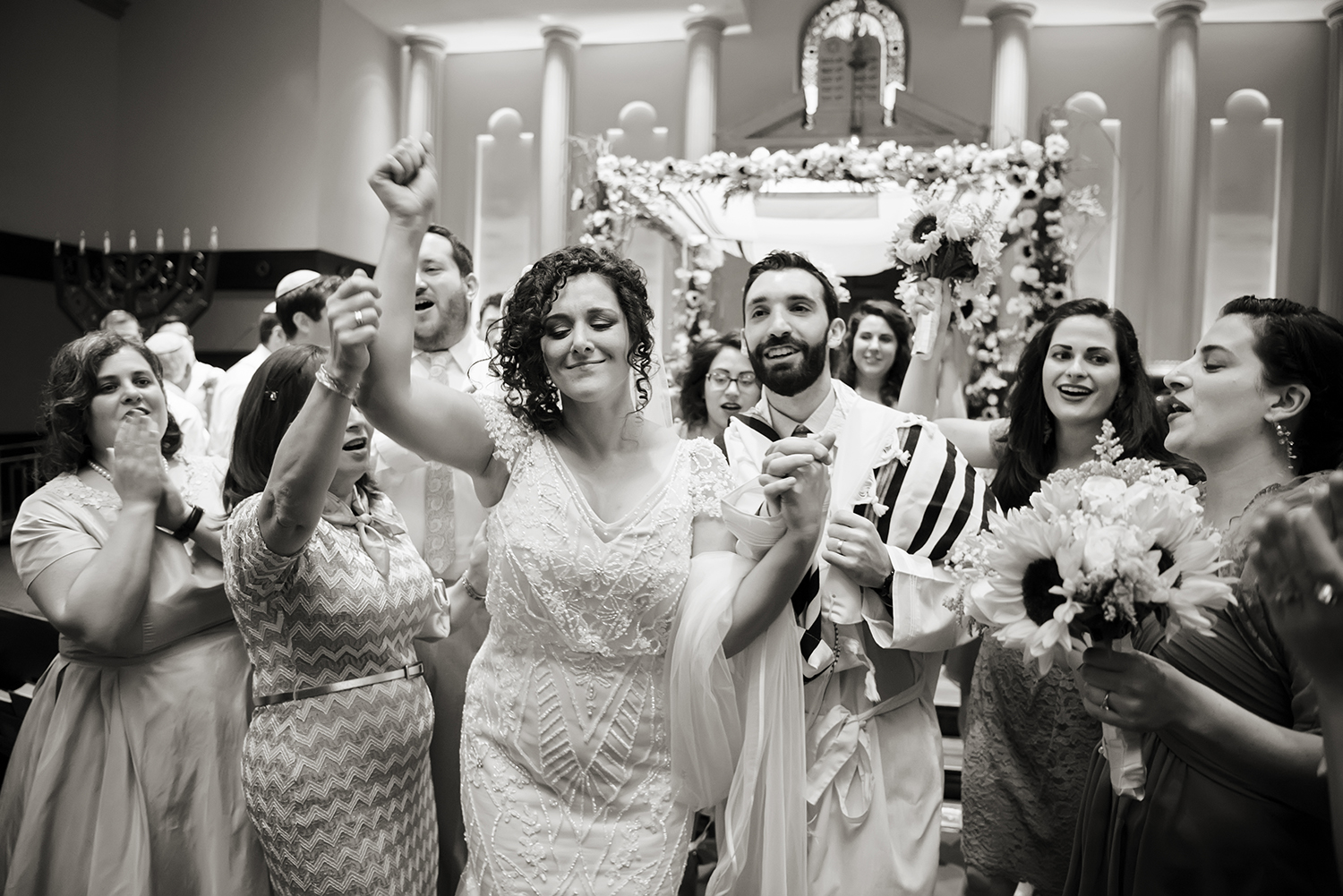 Bride and groom dance down the aisle after completion of their traditional Jewish wedding ceremony at Temple Emanu-El in Closter.