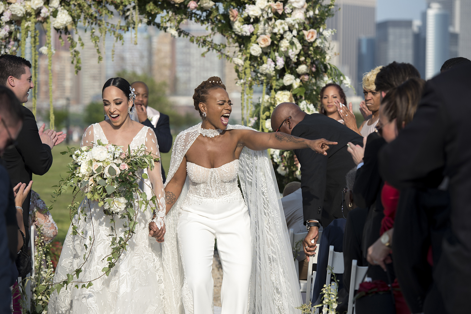 brides celebrating at the end of their Liberty House wedding ceremony in Jersey City. Jersey City wedding photographer