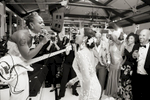 bride surprises her wife with a musical performance during their wedding reception at Liberty House in Jersey City