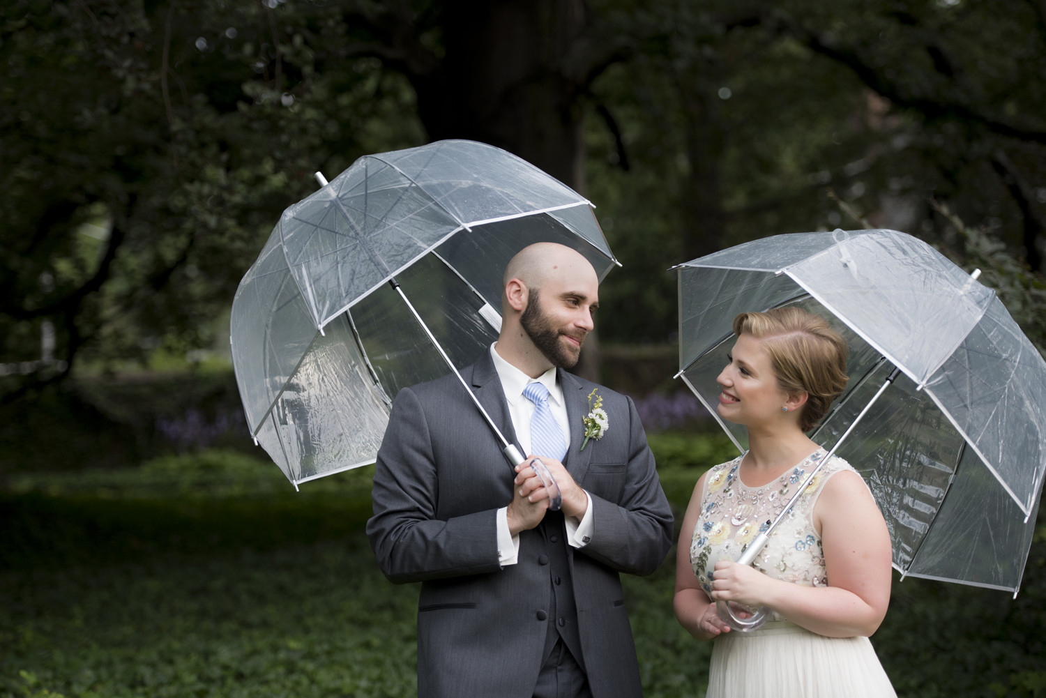 bride and groom with umbrellas on wedding day at Palmer House, Princeton. Princeton wedding photographer