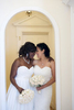 biracial brides under an arch on their wedding day. Lesbian wedding