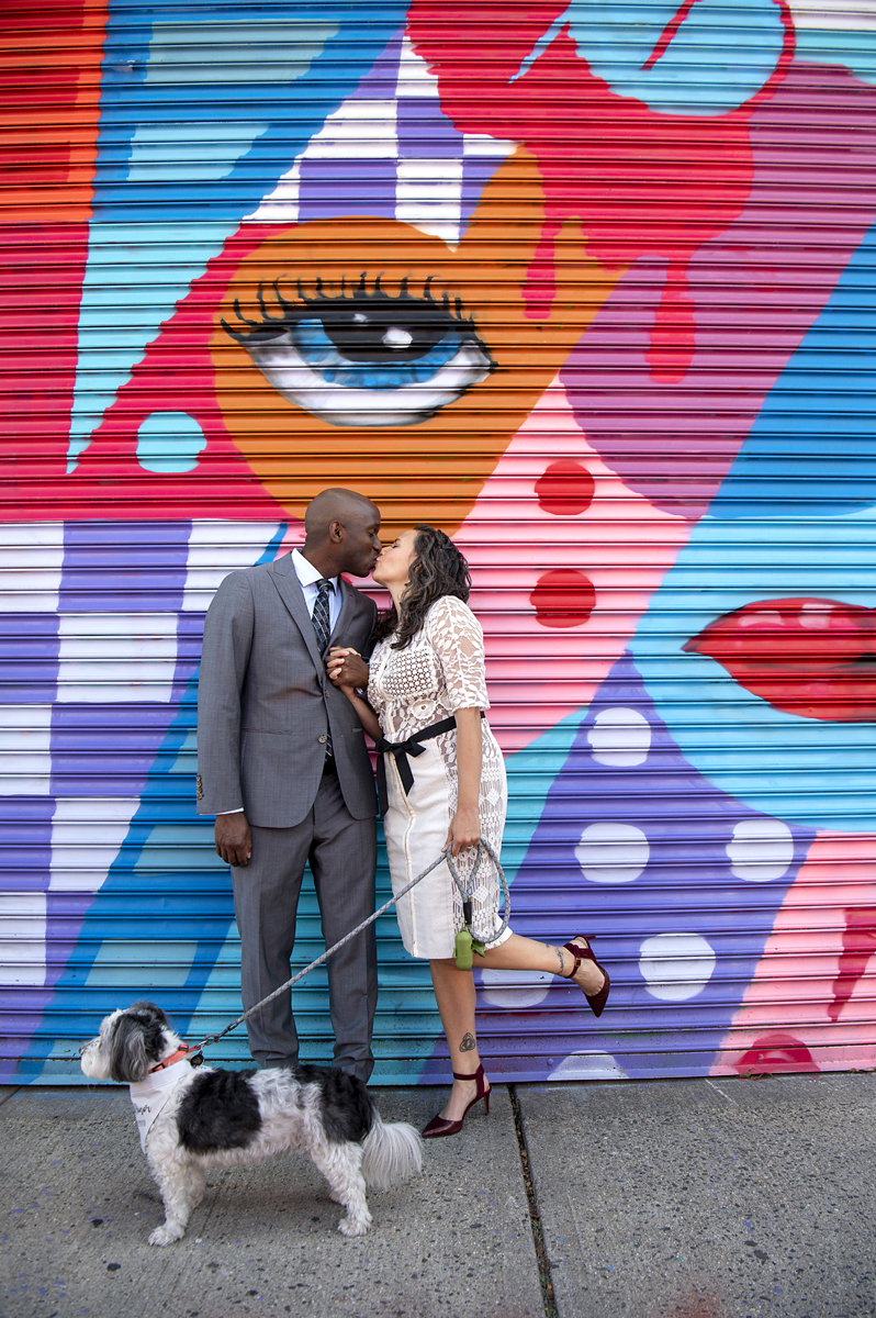 bride and groom kiss on Welling Court against one of the murals in Astoria, Queens with their dog in the foreground. Queens wedding photographer