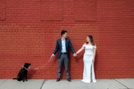 bride and groom and their dog pose for a portrait against a red wall on their wedding day in Astoria, Queens. Queens wedding photographer