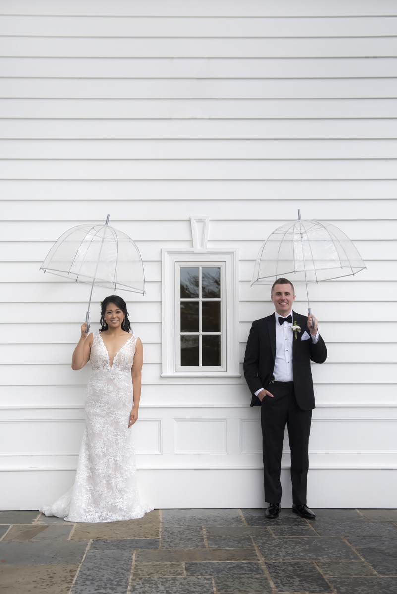 Portrait of bride and groom at Ryland Inn with umbrellas on their rainy wedding day.