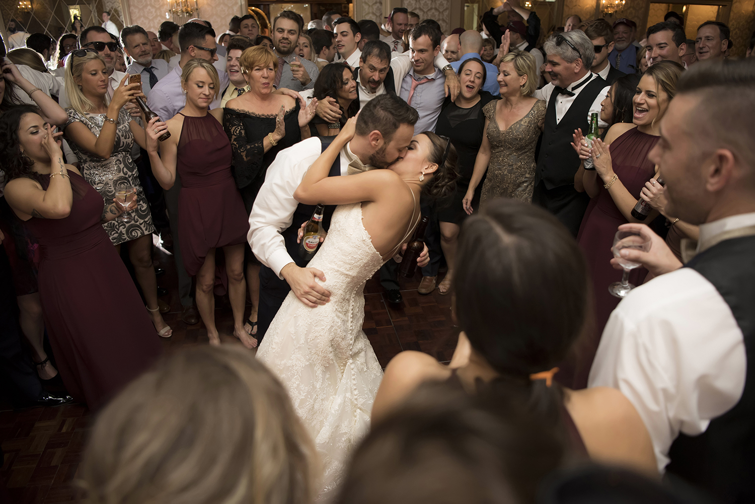 bride and groom kissing on the dance floor surrounded by family and friends at the end of their wedding at The Madison Hotel.